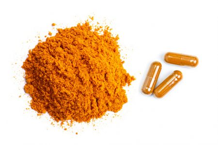 Pile of curcumin powder and Curcuma capsules isolated on white background. Health benefits and antioxidant food concept. Top view. Flat lay.